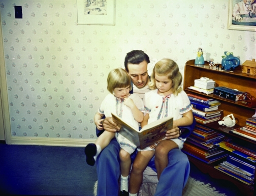 Walt Disney shares a story with his two daughters, Sharon and Diane.